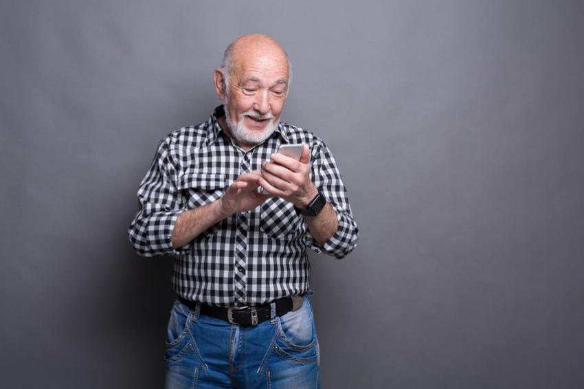 blije oudere man gebruikt mobiel internet